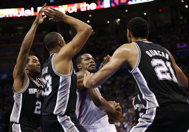 Oklahoma City Thunder forward Kevin Durant (35) attempts to drive between San Antonio Spurs forwards Kawhi Leonard (2), Boris Diaw (33), and Tim Duncan (21) during the first quarter of an NBA basketball game in Oklahoma City, Thursday, April 3, 2014. (AP Photo/Sue Ogrocki)