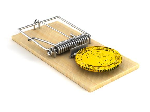 A physical gold bitcoin used as bait in a mouse trap.