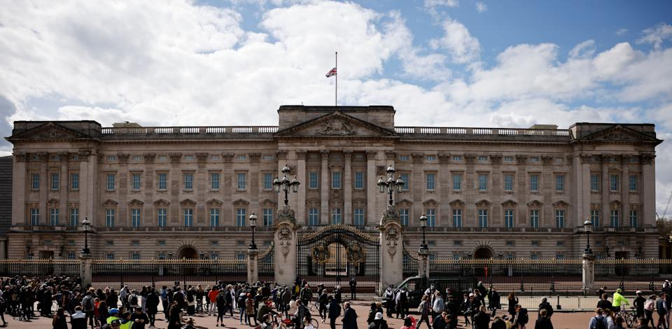 People gather outside Buckingham Palace where the Union Flag flies at half-mast in central London on April 9, 2021 after the announcement of the death of Britain's Prince Philip, Duke of Edinburgh. - Queen Elizabeth II's husband Prince Philip, who recently spent more than a month in hospital and underwent a heart procedure, died on April 9, 2021, Buckingham Palace announced. He was 99. (Photo by Tolga Akmen / AFP) (Photo by TOLGA AKMEN/AFP via Getty Images)