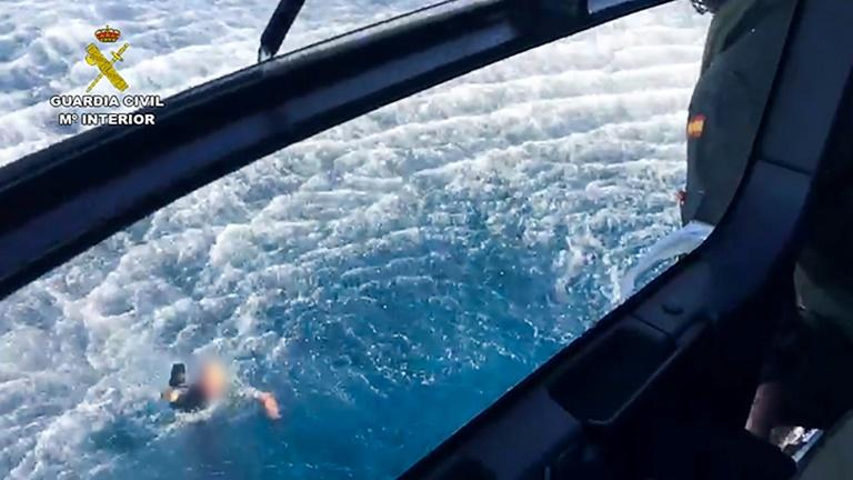 This handout picture released by the Spanish Guardia Civil shows a police officer swimming back to the police helicopter, after three Spanish police officers who were thrown into the sea when their boat crashed during a high-speed chase