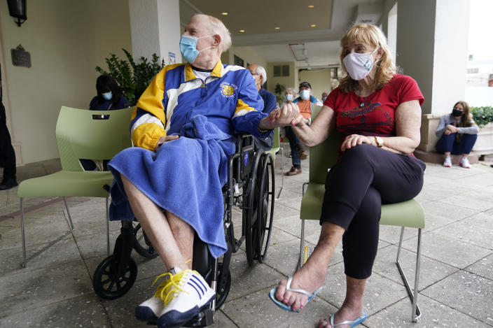 Residents Ken Fishman, 81, left, and Esther Wallach, 82, hold hands as they wait in line for the Pfizer-BioNTech COVID-19 vaccine at the The Palace assisted living facility, Tuesday, Jan. 12, 2021, in Coral Gables, Fla. (AP Photo/Lynne Sladky)