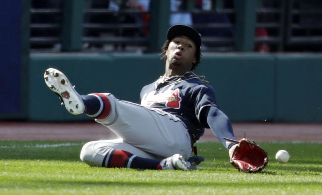 Atlanta Braves' Ronald Acuna Jr. dives for a ball hit by Cleveland Indians' Carlos Santana in the first inning during the first game of a baseball doubleheader, Saturday, April 20, 2019, in Cleveland. Santana was safe at first base and Jose Ramirez scored on the play. (AP Photo/Tony Dejak)