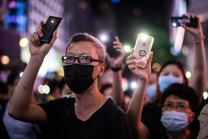 After the law came in, many Hong Kongers took to Twitter and other social media platforms such as Telegram and Signal to either announce their departure or share tips on internet safety (AFP Photo/Anthony WALLACE)