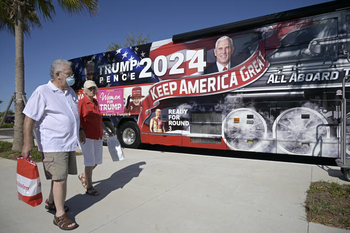 People walk past a bus wrapped with President Donald Trump photos during a Gaetz/Greene rally, Friday, May 7, 2021, in The Villages, Fla. (AP Photo/Phelan M. Ebenhack)