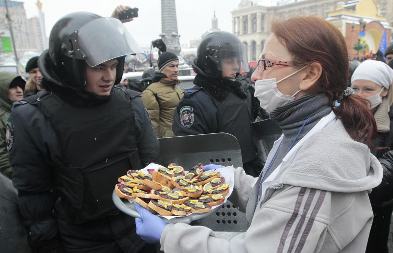 A Pro-European Union activist tries to give food to riot police officers preparing to block the Independence Square in KIev, Ukraine, Monday, Dec. 9, 2013. The policemen, wearing helmets and holding shields, formed a chain across Kiev's main street outside the city building. Organizers called on protesters to vacate the city hall and the other building which the opposition had used as its headquarters. (AP Photo/Sergei Chuzavkov)