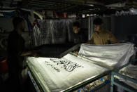 Workers hand print Taliban flags in a small workshop in Kabul's Jawid market, Afghanistan, Sunday, Sept. 12, 2021. The flag shop, tucked away in the courtyard of a Kabul market, has documented Afghanistan's turbulent history over the decades with its ever-changing merchandise. Now the shop is filled with white Taliban flags, emblazoned with the Quran's Muslim statement of faith, in black Arabic lettering. (AP Photo/Bernat Armangue)