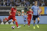 Toronto FC's Alejandro Pozuelo (10) kicks the ball away from New York City FC's Keaton Parks (55) during the second half of an MLS soccer match Wednesday, Sept. 11, 2019, in New York. The game ended in a 1-1 draw. (AP Photo/Frank Franklin II)