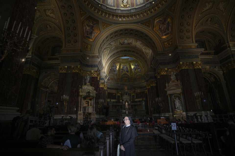 A nun is illuminated by sun beams inside the St. Stephen's Basilica in Budapest, Hungary, Friday, Sept. 10, 2021. Pope Francis is making his first foreign trip since undergoing intestinal surgery in July. His four-day visit to Hungary and Slovakia starting Sunday will not only test his health but also provide what may be one of the most awkward moments of his papacy — a meeting with Hungarian Prime Minister Viktor Orban, the sort of populist, right-wing leader Francis scorns. (AP Photo/Vadim Ghirda)