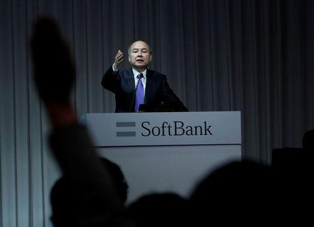 A journalist raises her hand to ask a question to Japan's SoftBank Group Corp Chief Executive Masayoshi Son during a news conference in Tokyo