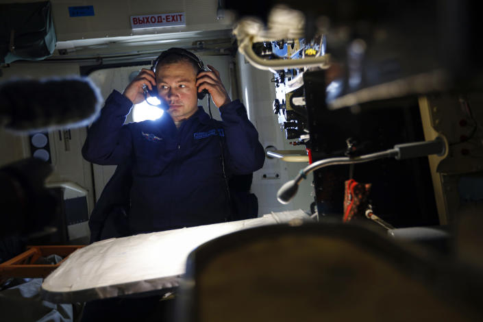 A Russian military cargo plane Il-76 crew member puts on headphones during a flight to the Alexandra Land island of the Franz Josef Land archipelago, Russia, Monday, May 17, 2021. Once a desolate home mostly to polar bears, Russia's northernmost military outpost is bristling with missiles and radar and its extended runway can handle all types of aircraft, including nuclear-capable strategic bombers, projecting Moscow's power and influence across the Arctic amid intensifying international competition for the region's vast resources. (AP Photo/Alexander Zemlianichenko)