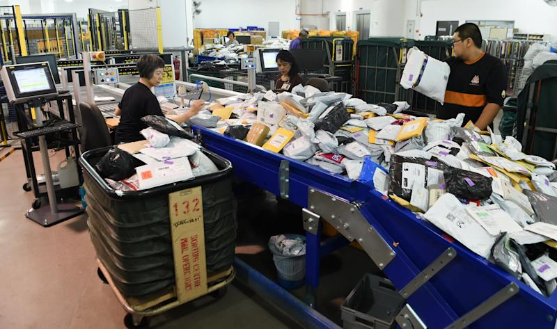 This photograph taken on January 12, 2016 shows employees of SingPost sorting out parcels at its centre in Singapore. SingPost was founded as the Singapore Post Office in 1819 shortly after Sir Stamford Raffles established the island as a British colony. SingPost, whose home market is just 5.5 million-strong, in 2003 decided to transform itself into an e-commerce and logistics company. / AFP / ROSLAN RAHMAN (Photo credit should read ROSLAN RAHMAN/AFP via Getty Images)