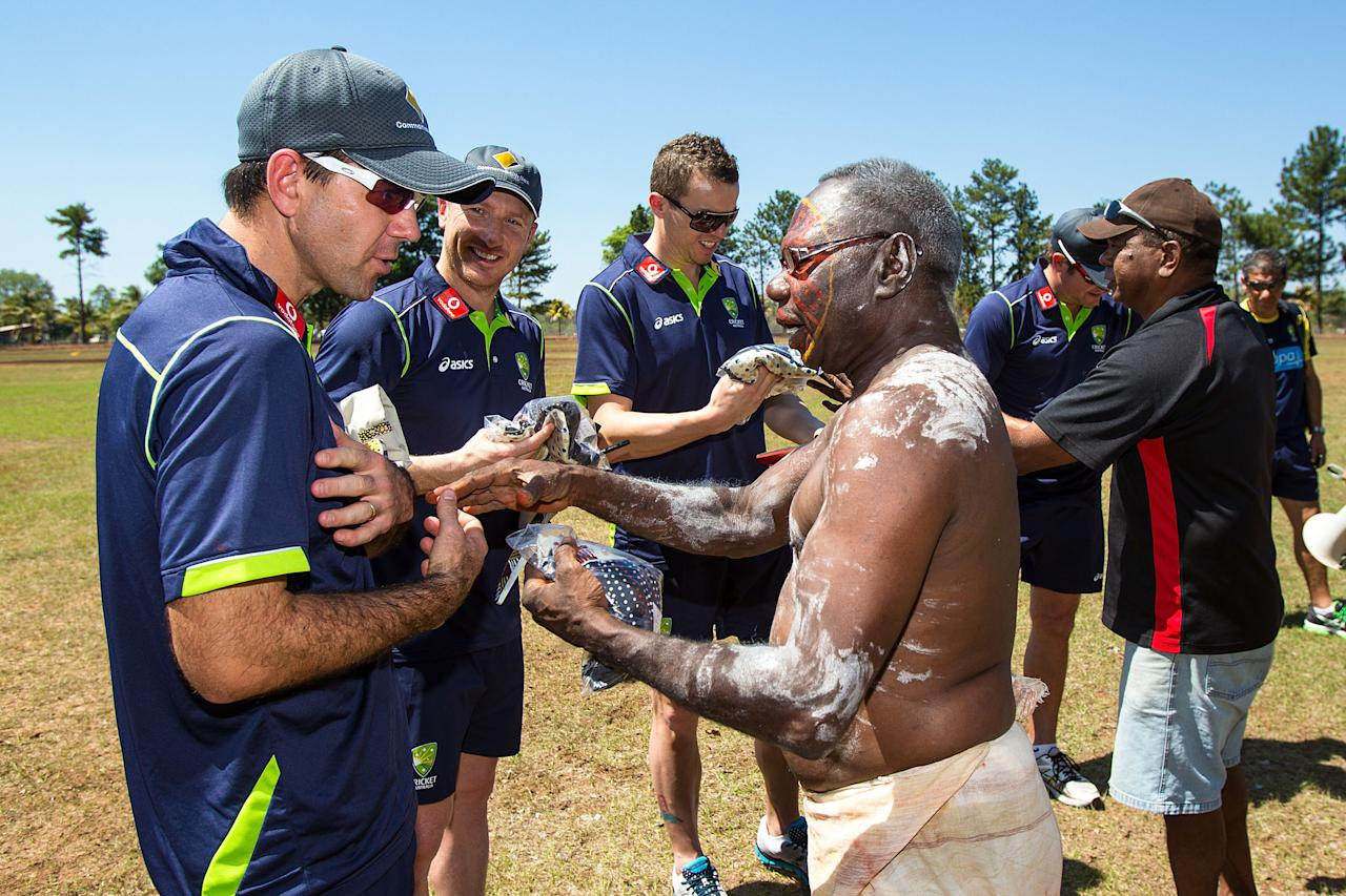 DARWIN, AUSTRALIA - AUGUST 10:  A tribal elder performs offers gifts to Ricky Ponting, Brad Haddin, Peter Siddle and Ryan Harris of the Australian cricket team during a visit to Pirlangimpi of the Tiwi Islands on August 10, 2012 on the Tiwi Islands, Australia.  (Photo by Mark Nolan/Getty Images)