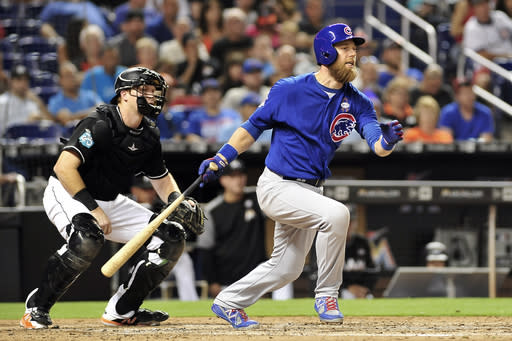 Chicago Cubs' Ben Zorbist, right, singles to right field in the sixth inning of a baseball game against the Chicago Cubs in Miami, Friday, March 30, 2018. (AP Photo/Gaston De Cardenas)