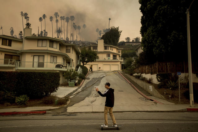 <p>A skateboarder passes a smoldering home as a wildfire burns in Ventura, Calif., on Tuesday, Dec. 5, 2017. (Photo: Noah Berger/AP) </p>