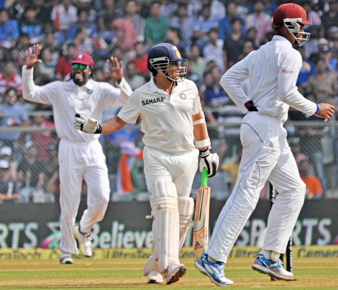 West Indian players celebrate as master blaster Sachin Tendulkar walks back to pavilion after scoring 74 runs during the 2nd day of the 2nd Test Match between India and West Indies at Wankhede Stadium in Mumbai on Nov.15, 2013. (Photo:IANS)