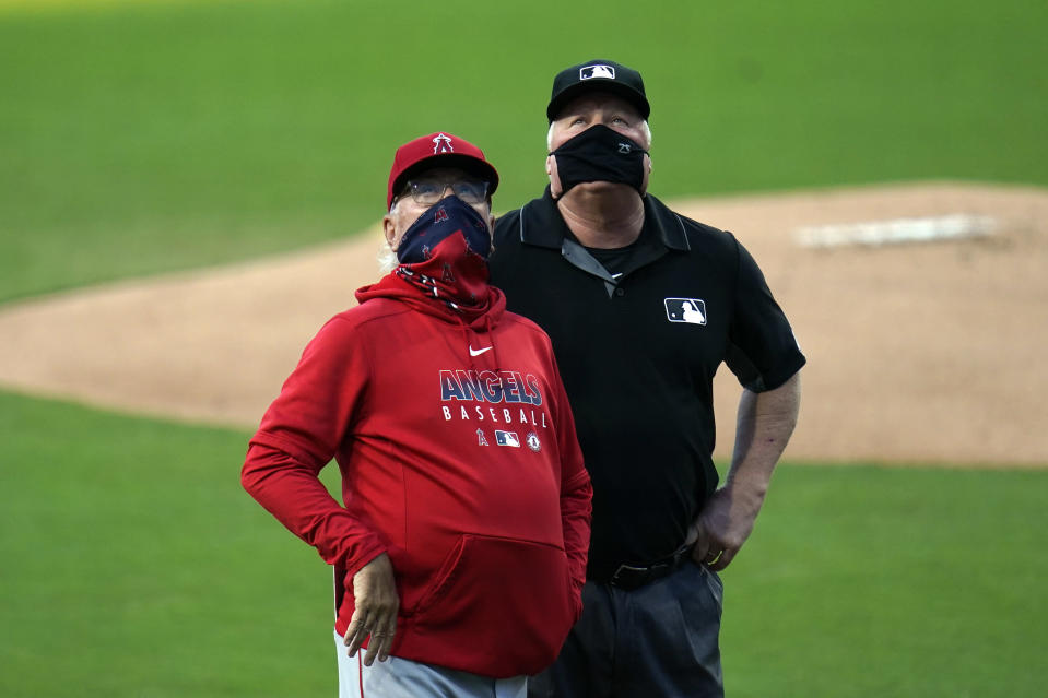 Los Angeles Angels manager Joe Maddon, left, looks up alongside second base umpire Bill Miller as they wait for lights to be turned on at Petco Park during the first inning of a baseball game against the San Diego Padres, Tuesday, Sept. 22, 2020, in San Diego. (AP Photo/Gregory Bull)