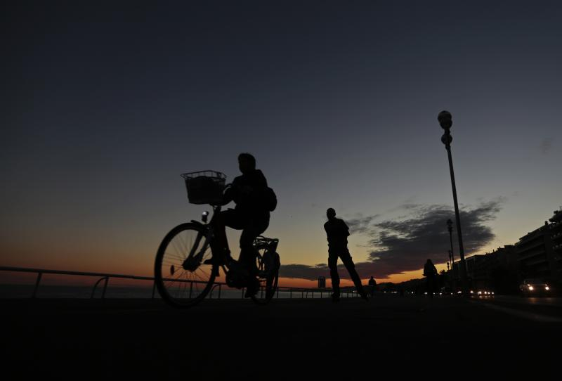 A woman rides her bike at sunset on the beach front in Nice