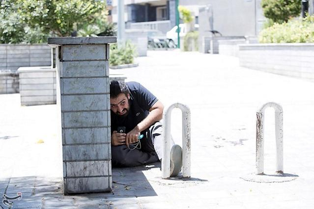 <p>A man takes cover during an attack on the Iranian parliament in central Tehran, Iran, June 7, 2017. (Photo: Tasnim News Agency/Handout via Reuters) </p>
