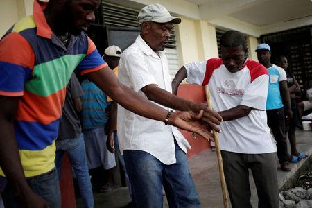 Two men help a man with visual impairment during the eviction of residents from a shelter for people displaced by Hurricane Matthew in Lycee Jean Claude Museau, which will be used as a voting centre, before the election in Les Cayes, Haiti, November 19, 2016. REUTERS/Andres Martinez Casares