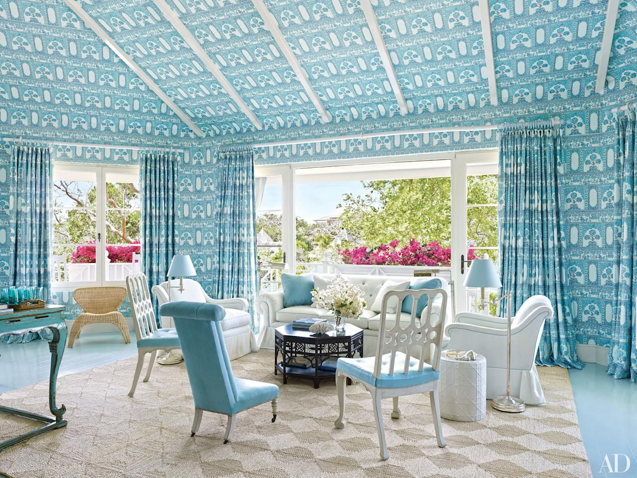 """New York designer Miles Redd recast the interiors of a Texas family's <a rel=""""nofollow"""" href=""""http://www.architecturaldigest.com/story/miles-redd-bahamas-beach-vacation-home-article?mbid=synd_yahoo_rss"""">vacation house at the Lyford Cay club in the Bahamas</a>. The living room walls and ceiling are covered in a China Seas fabric, with curtains to match. The sofa is by Oscar de la Renta Home for Century Furniture, and the antique slipper chair is clad in a blue Global Leathers hide."""