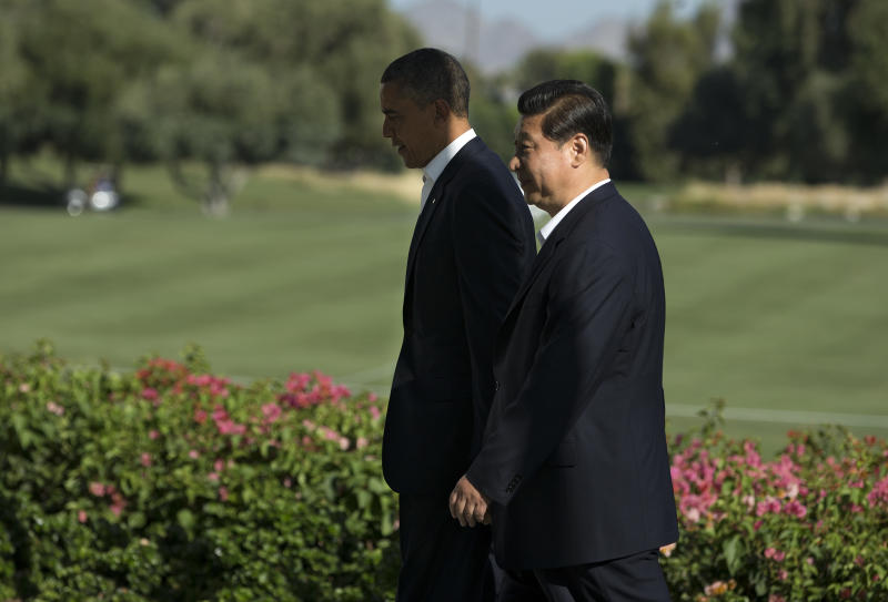 President Barack Obama walks with Chinese President Xi Jinping at the Annenberg Retreat at Sunnylands as they meet for talks Friday, June 7, 2013, in Rancho Mirage, Calif. Seeking a fresh start to a complex relationship, the two leaders are retreating to the sprawling desert estate for two days of talks on high-stakes issues, including cybersecurity and North Korea's nuclear threats. (AP Photo/Evan Vucci)