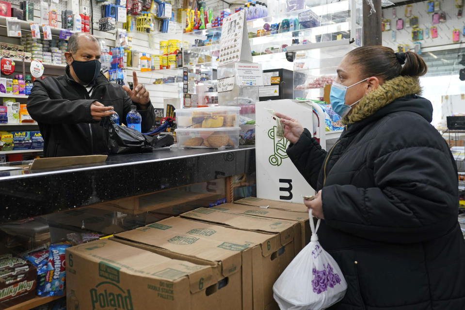 Bodega owner Francisco Marte, left, assists a customer with her purchase, Wednesday, Feb. 10, 2021, in the Bronx borough of New York. Marte heads up the Bodega and Small Business Group, which represents bodegas in New York. Francisco Marte, president of the Bodega and Small Business Association of New York, said said he has been lobbying local officials to set aside appointments for bodega workers, many of whom are unaware they are eligible.(AP Photo/Kathy Willens)