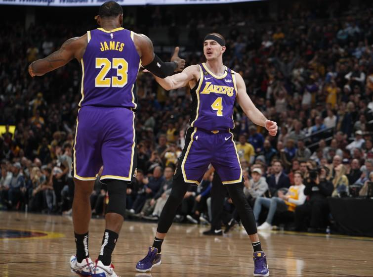 Lakers forward LeBron James congratulates guard Alex Caruso (4) after he scored late in the second half against the Nuggets in a game Feb. 12, 2020, in Denver.