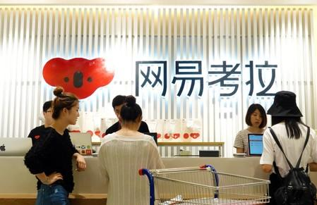 People are seen at the check-out counter of a physical store of Netease's e-commerce platform Kaola, in Zhengzhou