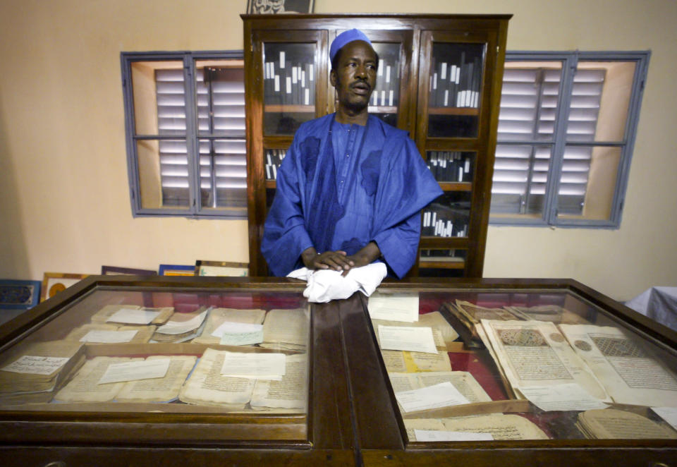In this photo taken Tuesday, Mar. 16, 2004, an unidentified worker looks after some of the 20,000 preserved ancient Islamic manuscripts which rest in air-conditioned rooms at the Ahmed Baba Institute in Timbuktu, Mali. Islamist extremists torched the library containing the historic manuscripts in Timbuktu, the mayor of the town said Monday, Jan. 28, 2013, while owners have succeeded in removing some of the manuscripts from Timbuktu to save them and others have been carefully hidden away from the Islamists. (AP Photo/Ben Curtis)
