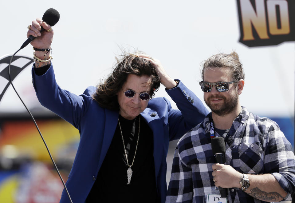 Entertainer Ozzy Osbourne, left, and his son Jack acknowledge cheers from fans during a ceremony before a NASCAR Cup Series auto race at Texas Motor Speedway in Fort Worth, Texas, Sunday, April 9, 2017. (AP Photo/Tony Gutierrez)