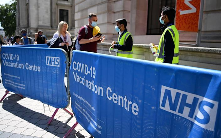 People queue at a Covid-19 vaccination centre in London - Andy Rain/Shutterstock