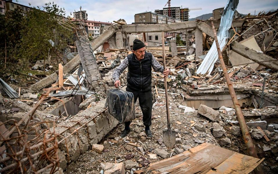 Retired police officer Genadiy Avanesyan, 73, searches for belongings in the remains of his house, which is said was destroyed by Azeri shelling
