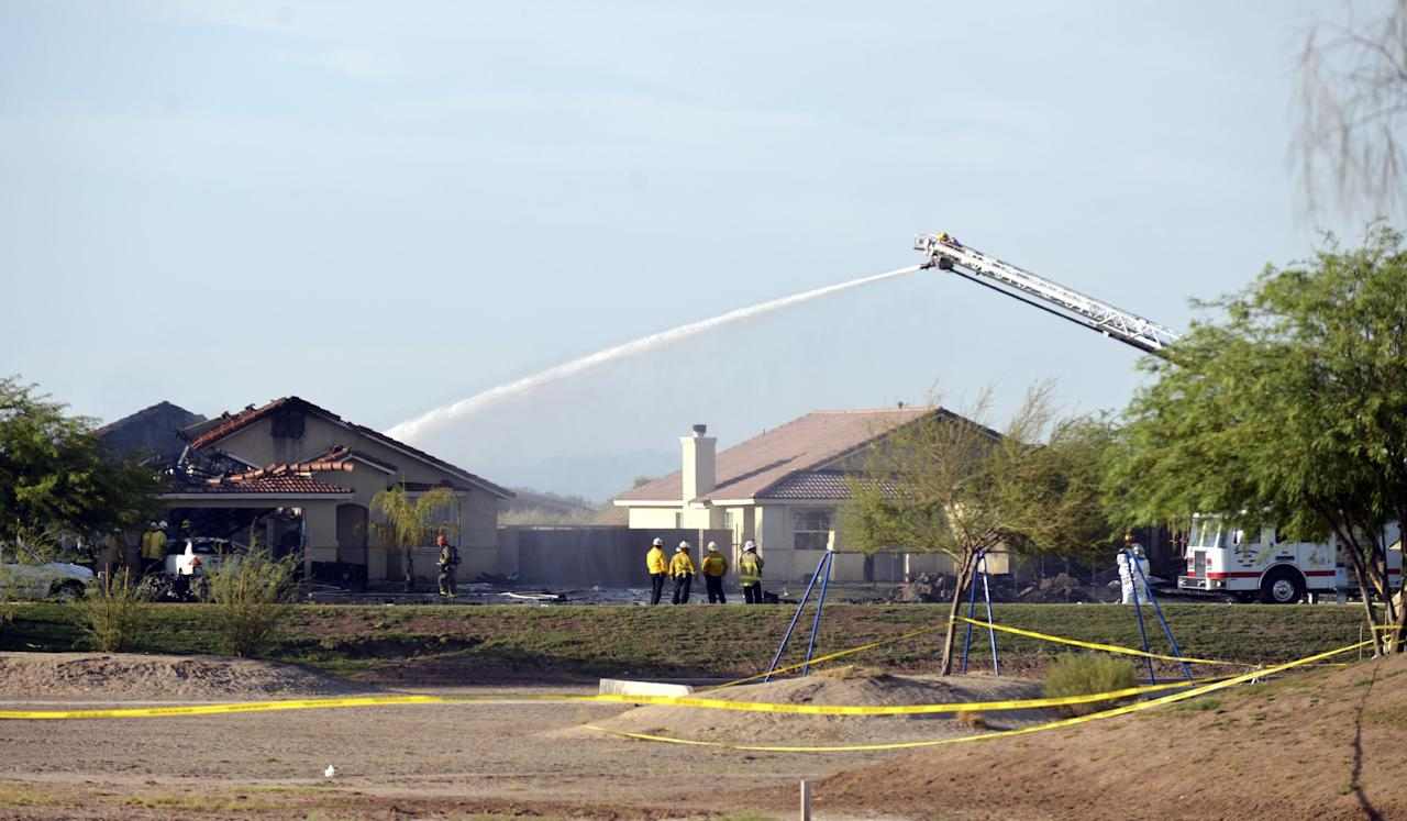Water is sprayed onto buildings after a Marine jet crashed into a residential area in the desert community of Imperial, Calif., setting two homes on fire Wednesday, June 4, 2014. The pilot ejected safely, and there was no immediate word of any injuries on the ground. The Harrier AV-8B went down at 4:20 p.m. in Imperial, a city of about 15,000 near the U.S.-Mexico border about 90 miles east of San Diego. AP Photo/Imperial Valley Press, Chelcey Adami)