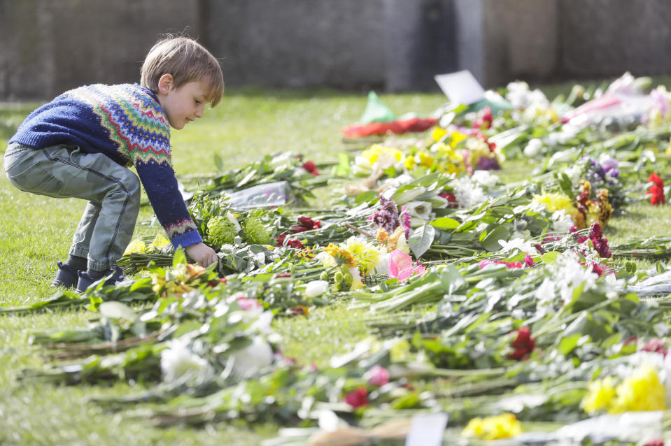 A child lays flowers outside the Cambridge gate of Windsor Castle in Windsor, England after the announcement regarding the death of Britain's Prince Philip, Friday, April 9, 2021. Buckingham Palace officials say Prince Philip, the husband of Queen Elizabeth II, has died. He was 99. Philip spent a month in hospital earlier this year before being released on March 16 to return to Windsor Castle. (AP Photo/Kirsty Wigglesworth)