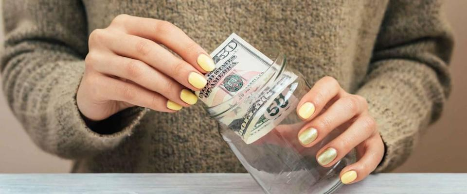 Girl in brown sweater with yellow manicure puts money in a glass jar, close-up
