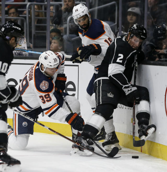 Los Angeles Kings defenseman Paul LaDue (2) battles for the puck with Edmonton Oilers right wing Alex Chiasson (39) and left wing Jujhar Khaira (16) during the first period of an NHL hockey game in Los Angeles, Sunday, Nov. 25, 2018. (AP Photo/Alex Gallardo)