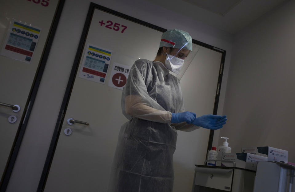 A Belgian Army medic suits up as she prepares to bring lunch to a patient with COVID-19 at the St. Michiel Hospital in Brussels, Tuesday, Nov. 24, 2020. The Belgian military has been called into several hospitals and care homes to alleviate the stress on healthcare personnel. (AP Photo/Virginia Mayo)