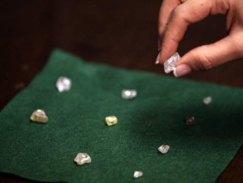 FILE PHOTO - A visitor holds a 17 carat diamond at a Petra Diamonds mine in Cullinan