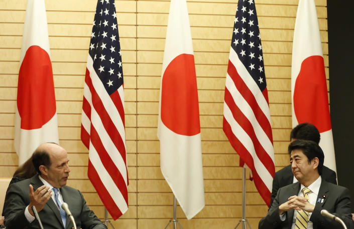 Japan's Prime Minister Shinzo Abe (R) and ex-US ambassador to Japan John Roos (L) pictured announcing the return of some US bases on Okinawa, in April 2013 (AFP Photo/Issei Kato)