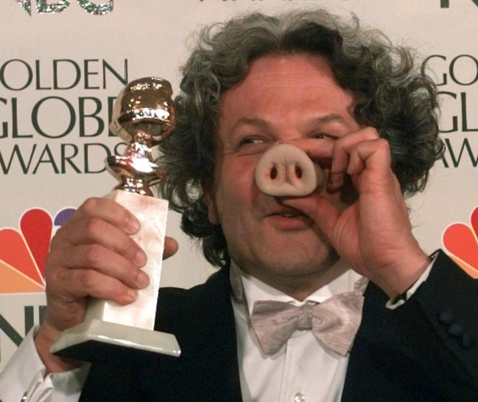"""Producer George Miller sports a pig nose as he holds his award for Best Motion Picture - Musical or Comedy for """"Babe"""" at the Golden Globe Awards, Sunday, Jan. 21, 1996, in Beverly Hills, Calif. (AP Photo/Mark J. Terrill)"""