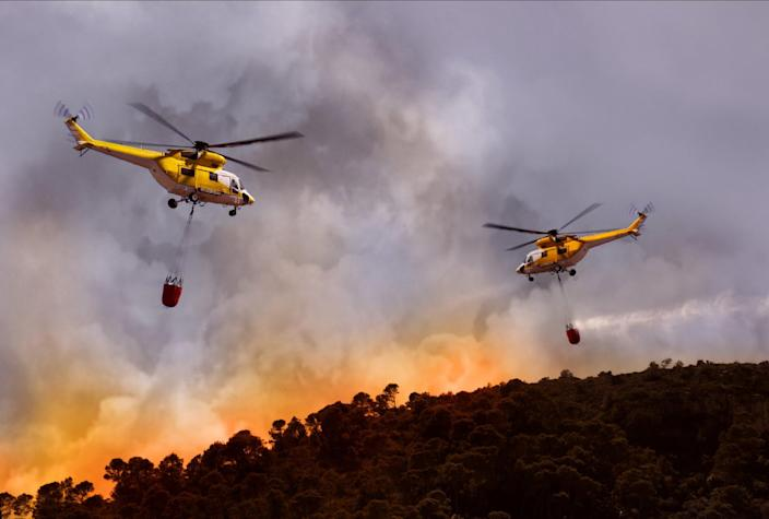 Two helicopters drop water buckets into the heart of blazing wildfires.