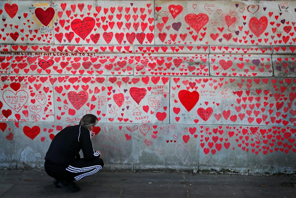 <p>A man paints a heart on the National Covid Memorial Wall in London</p> (AP)