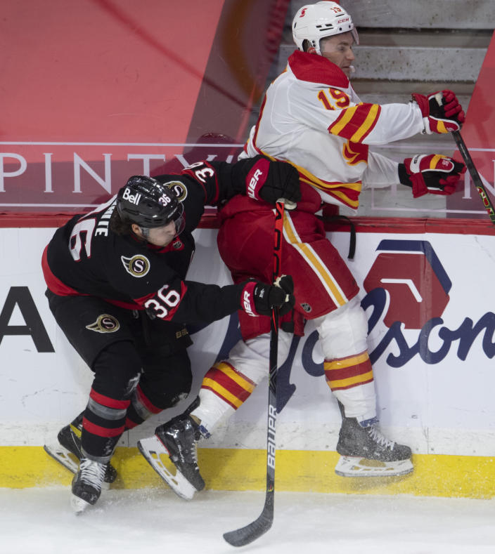 Ottawa Senators center Colin White collides with Calgary Flames left wing Matthew Tkachuk along the boards during the first period of an NHL hockey game Thursday, Feb. 25, 2021, in Ottawa, Ontario. (Adrian Wyld/The Canadian Press via AP)
