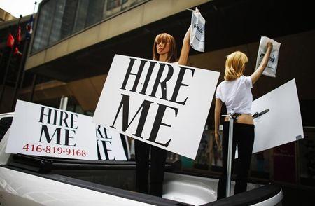 """Motorized mannequins hold signs that read """"Hire Me"""" in Toronto"""