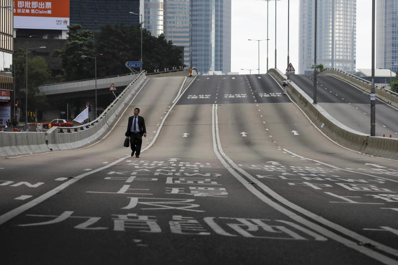FILE - In this June 17, 2019, file photo, a man walks alone on normally busy road near the Legislative Council after protesters continue to protest against the extradition bill in Hong Kong. Hong Kong's embattled leader Carrie Lam said Tuesday that the city's economy is being battered by months of increasingly violent protests. (AP Photo/Vincent Yu, File)