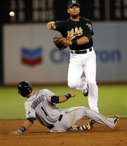 Tampa Bay Rays' Sean Rodriguez is forced at second base by Oakland Athletics' Brandon Hicks, who then completed the double play, in the sixth inning of a baseball game in Oakland, Calif., Tuesday, July 31, 2012. (AP Photo/Dino Vournas)
