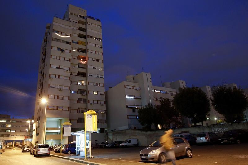A man walks past a residential building in Rome