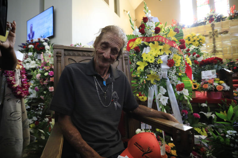 'His world': Bosco sits next to a wreath honouring his 22 years of marriage to Margie at La Paz Faith in Texas