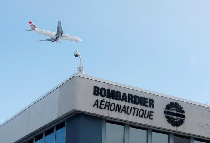 FILE PHOTO - A plane flies over a Bombardier plant in Montreal