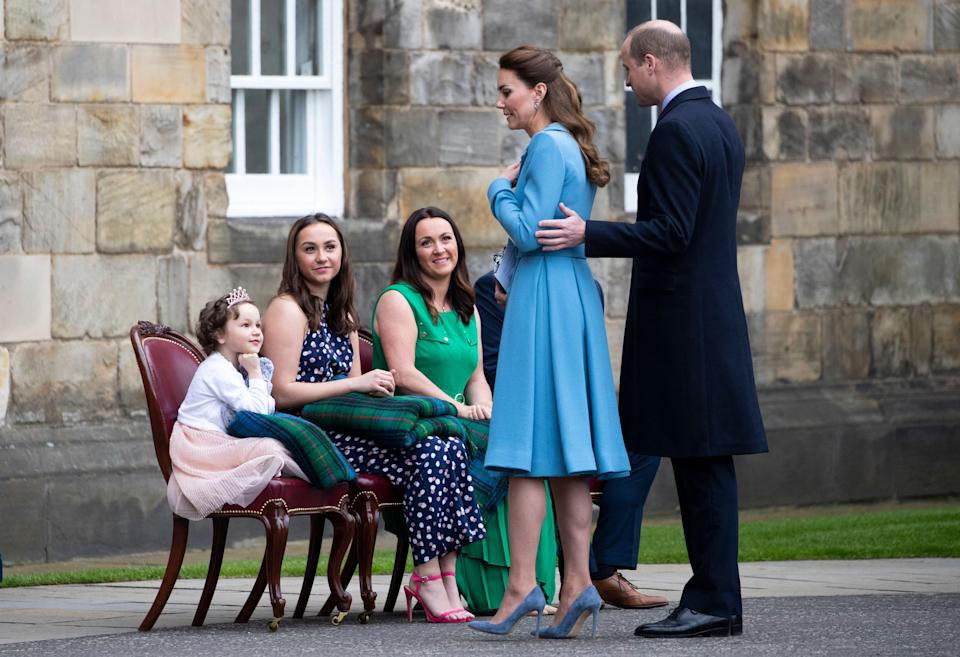 Five year-old cancer patient Mila Sneddon (L), who features in an image from the Hold Still photography project, speaks to Britain's Prince William, Duke of Cambridge and Britain's Catherine, Duchess of Cambridge as she and her family attend a Beating Retreat by The Massed Pipes and Drums of the Combined Cadet Force in Scotland as special guests of the Royal couple, at the Palace of Holyroodhouse in Edinburgh, Scotland on May 27, 2021, the final day of their week-long visit to the country. (Photo by Jane Barlow / POOL / AFP) (Photo by JANE BARLOW/POOL/AFP via Getty Images)